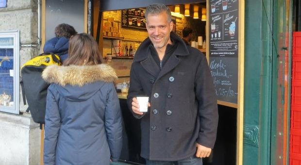 man smiling and drinking coffee