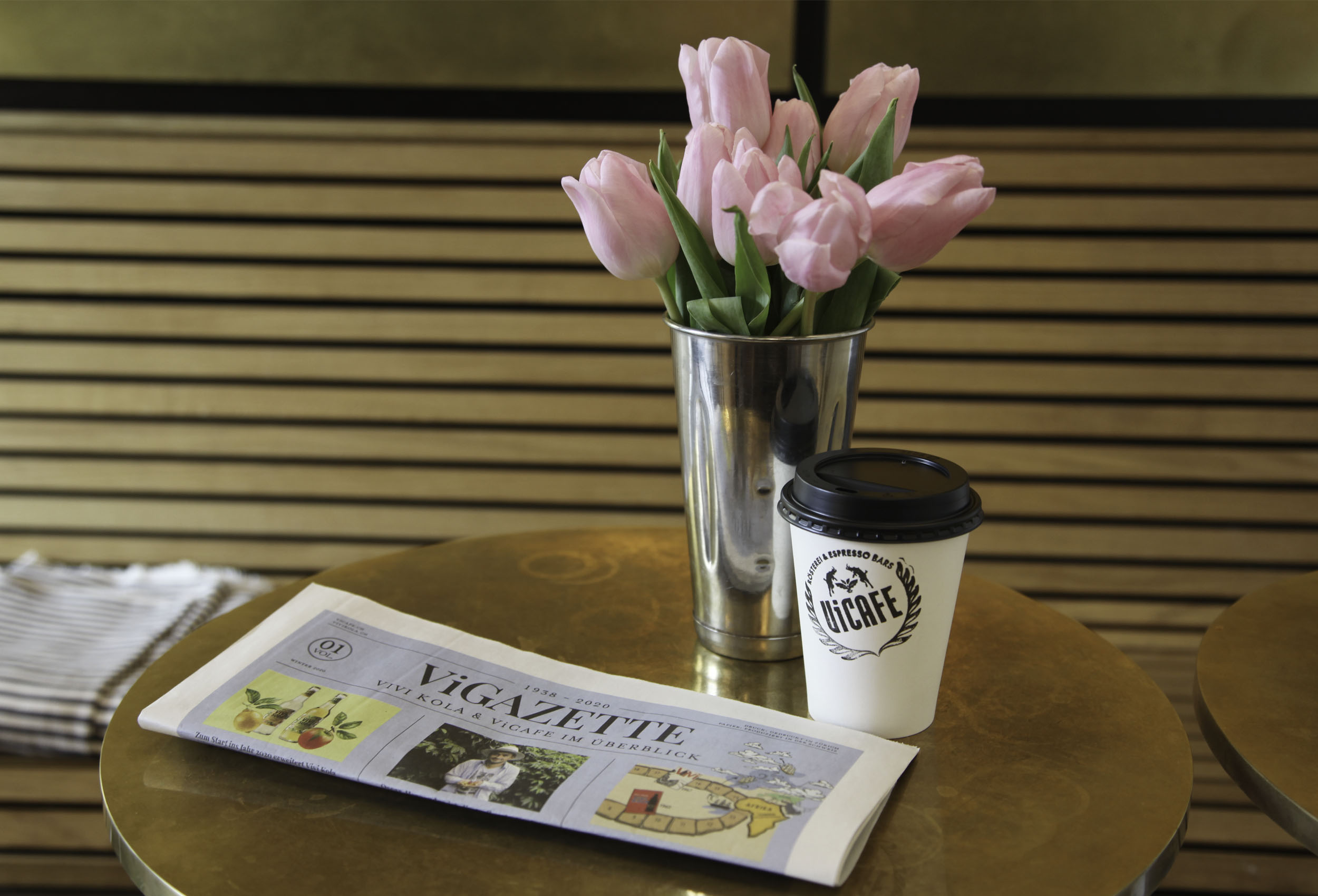 Vigazette newspaper, vicafe coffee and flowers on golden table