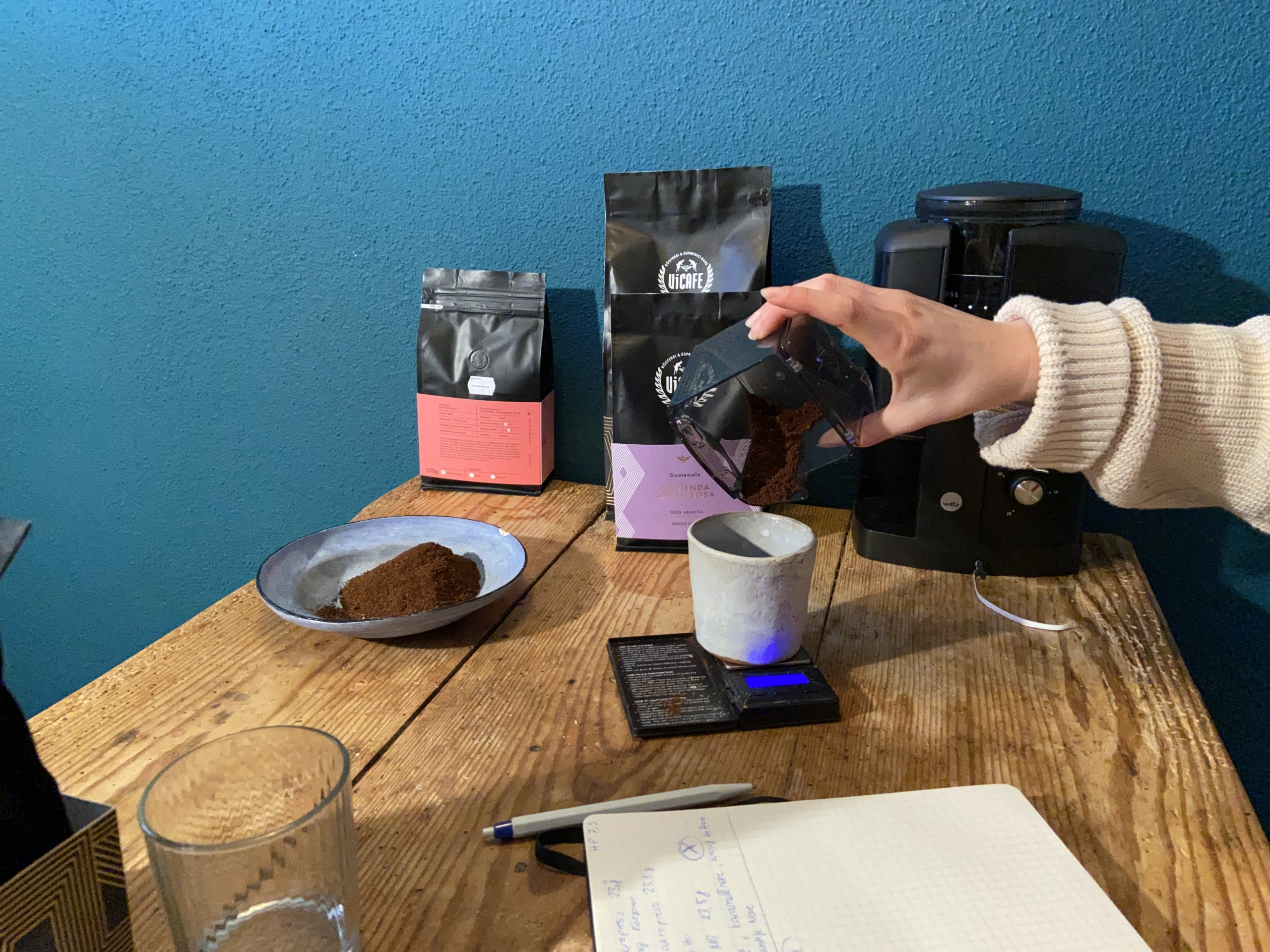 hand measuring coffee on scale