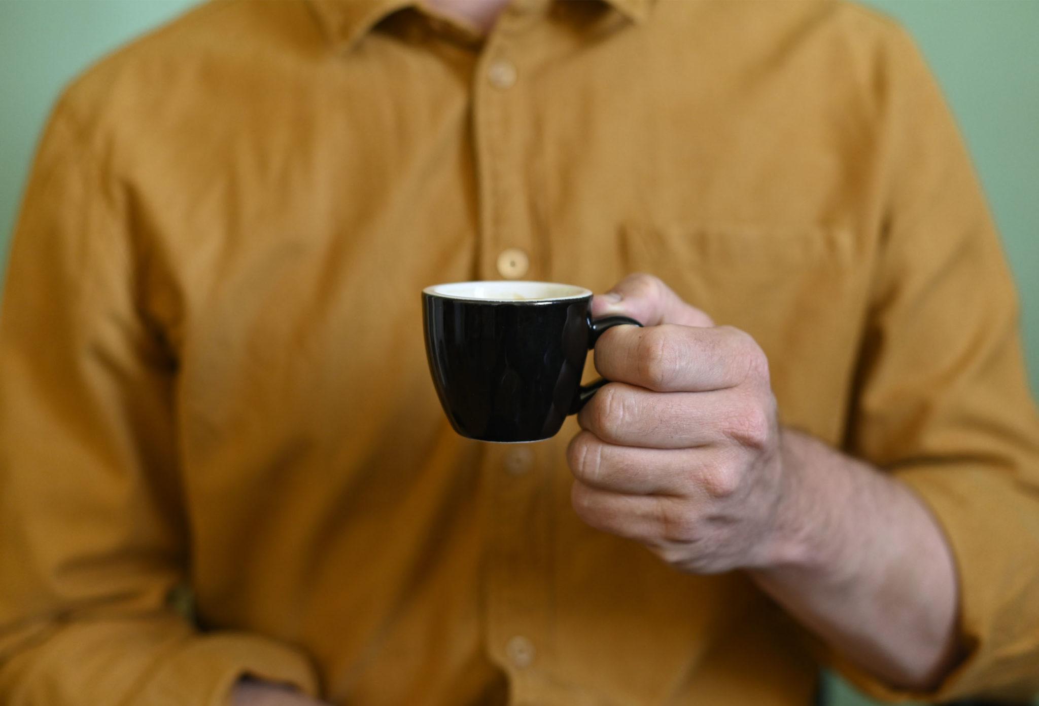 man holding a black espresso cup
