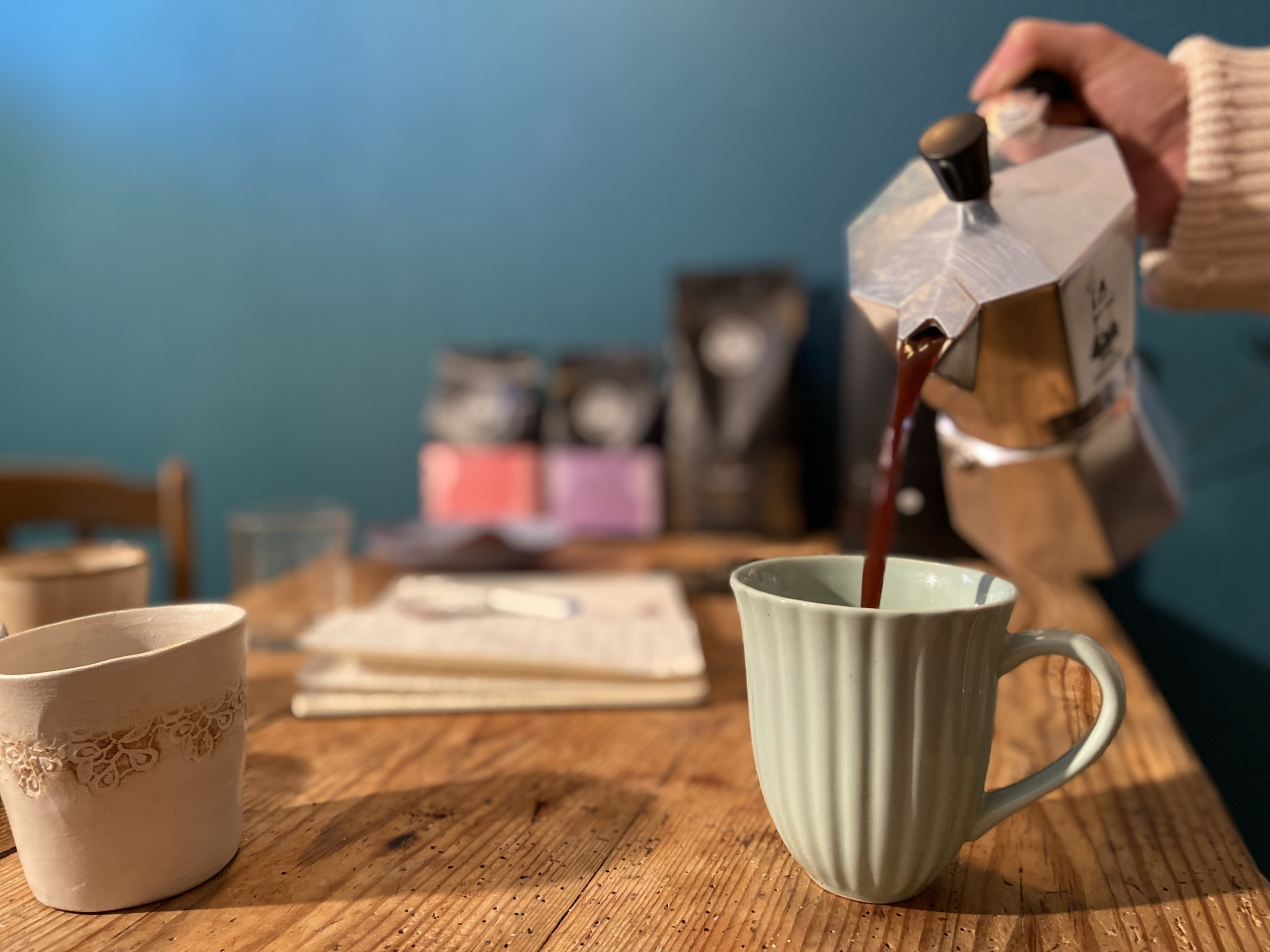 hand pouring coffee from bialetti can to cup