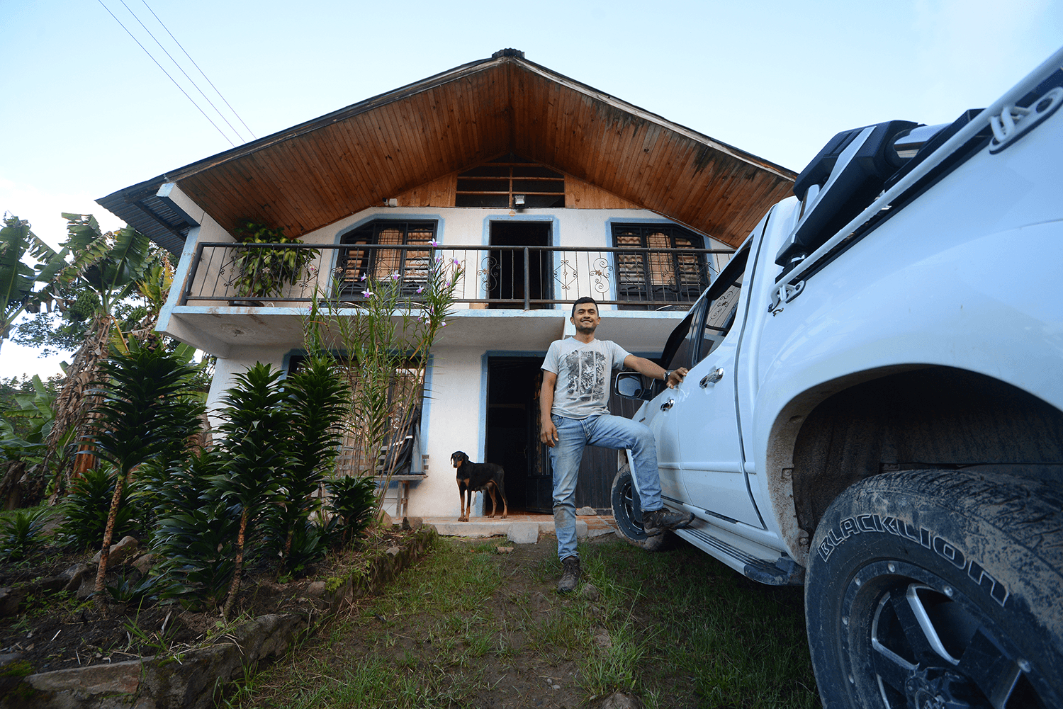 colombian coffee farmer in front of his house